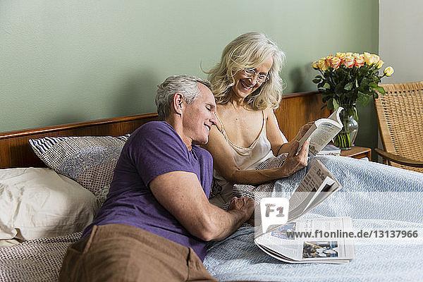 Fröhliche Frau zeigt dem Mann ein Buch  während sie zu Hause auf dem Bett sitzt