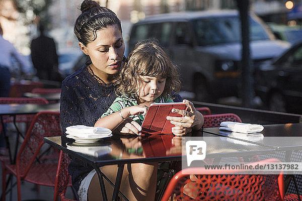 Familie benutzt Tablet-Computer im Straßencafé