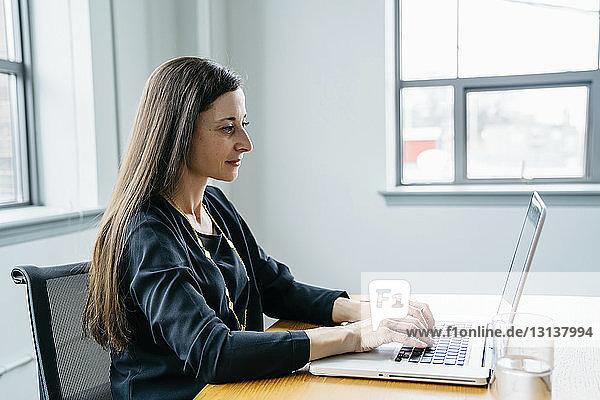 Seitenansicht einer Geschäftsfrau  die im Büro an einem Laptop-Computer arbeitet