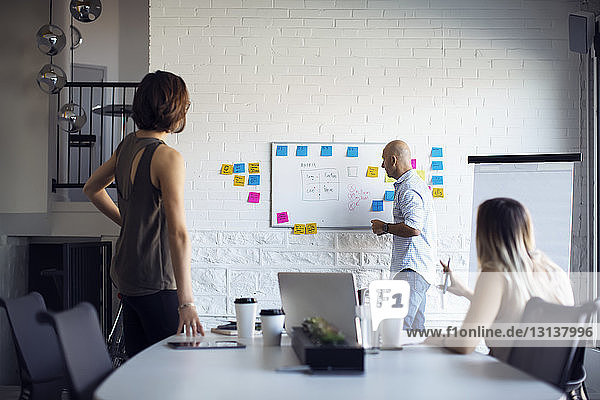 Businessman planning with female colleagues during meeting in creative office