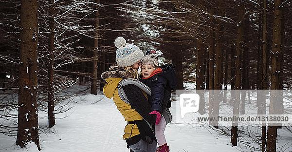 Mutter trägt Tochter  während sie im Winter im Wald steht