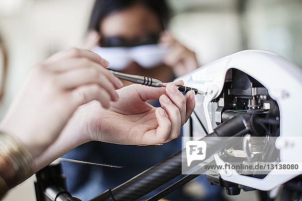 Cropped image of female student working on drone with friend in background