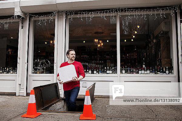 Kleinunternehmer hält Paket beim Verlassen des unterirdischen Lagers vor dem Weinladen