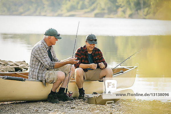 Friends with fishing rods talking while sitting on boat by lake