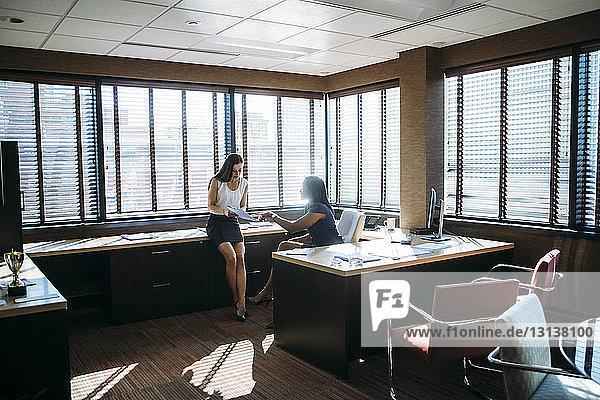 Weibliche Kollegen diskutieren Berichte im Büro