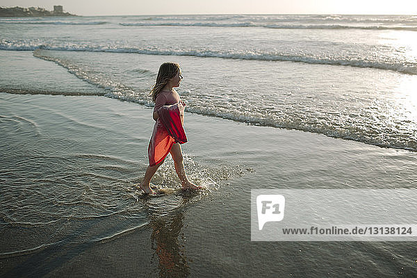 High angle view of girl holding dress while walking towards sea at beach