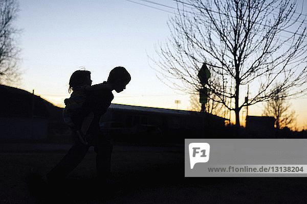 Silhouettenbruder nimmt seine Schwester huckepack  während er bei Sonnenuntergang gegen den Himmel läuft