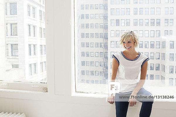 Glückliche junge Frau sitzt zu Hause auf der Fensterbank vor Gebäuden