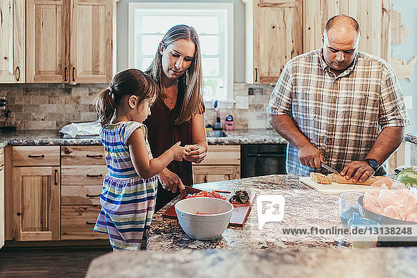 Parents preparing food while standing with daughter in kitchen at home