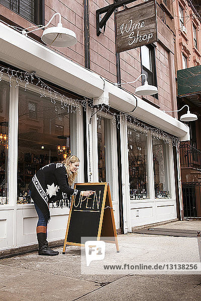 Full length side view of female small business owner making open sign outside wine shop