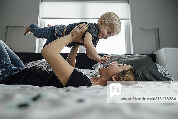 Side view of happy mother picking up son while lying on bed at home