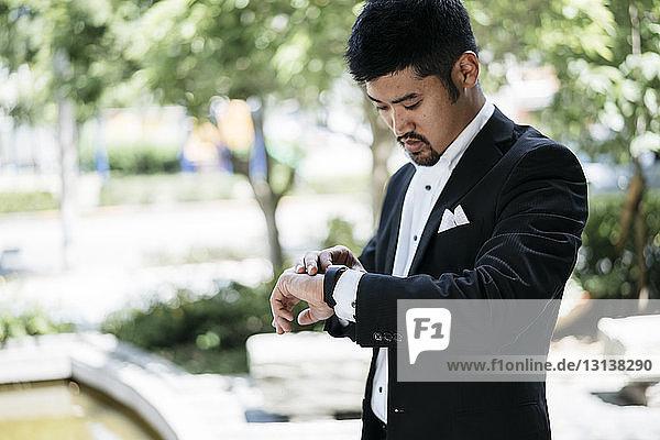 Junger Geschäftsmann kontrolliert die Zeit auf einer intelligenten Uhr in der Stadt