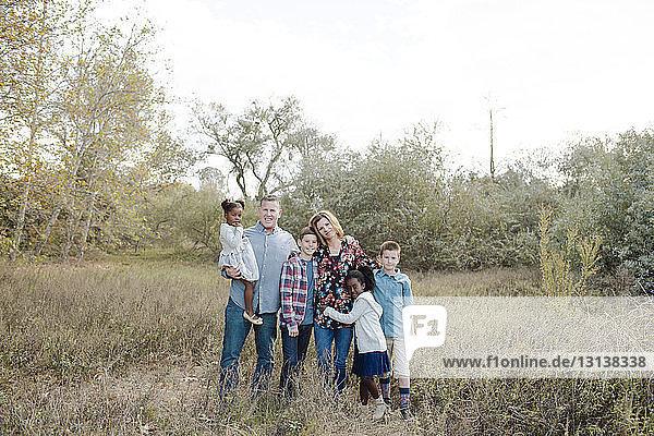 Porträt einer glücklichen Familie  die auf einem Feld im Park gegen den Himmel steht