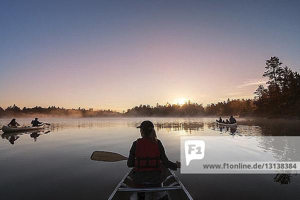 Rückansicht einer Frau  die in einem Boot auf einem ruhigen See vor blauem Himmel reist