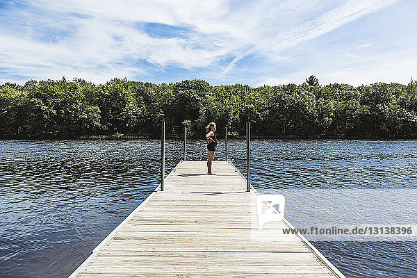 Side view of girl standing on jetty over lake against sky