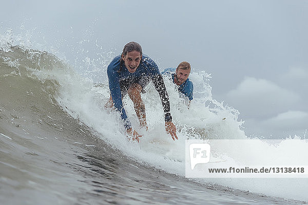 Portrait of friends surfing on sea against cloudy sky