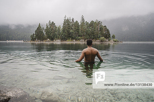 Shirtless man swimming in lake at forest