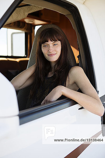 Portrait of young woman with hands behind head in camper van