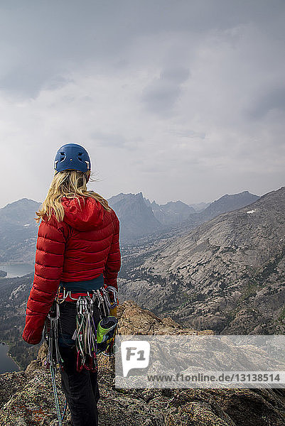 Female hiker with mountain climbing equipment looking at view while standing on cliff against sky