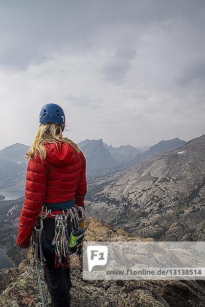 Bergsteigerin mit Bergsteigerausrüstung schaut auf die Aussicht  während sie am Fels gegen den Himmel steht