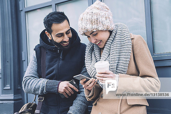 Happy couple using mobile phone while leaning by building in city