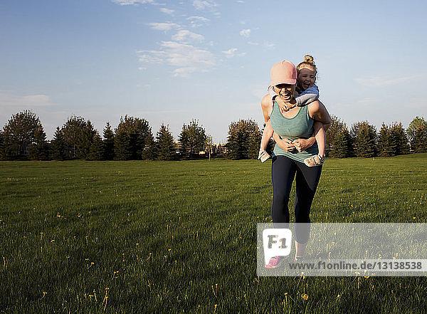 Glückliche Mutter nimmt ihre Tochter huckepack  während sie im Park auf einem Grasfeld gegen den Himmel trainiert