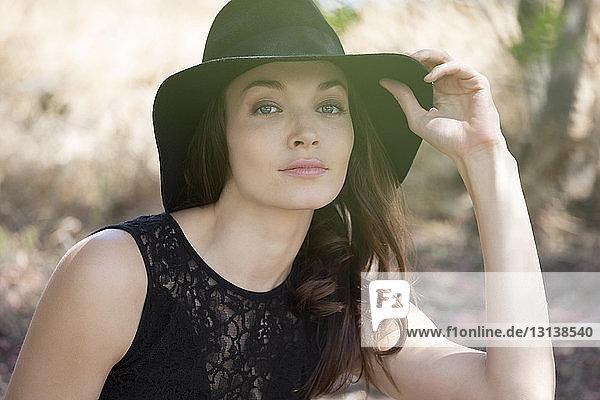 Portrait of beautiful woman wearing black hat and dress