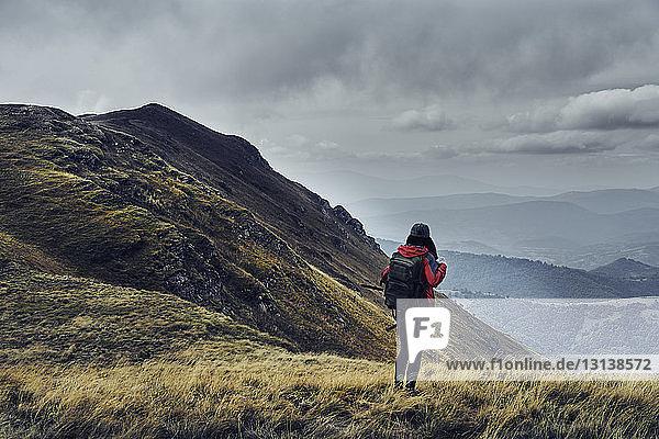 Rückansicht einer Wanderin mit Rucksack auf dem Balkangebirge vor bewölktem Himmel stehend