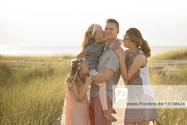 Portrait of confident father with loving family standing on grassy field during summer