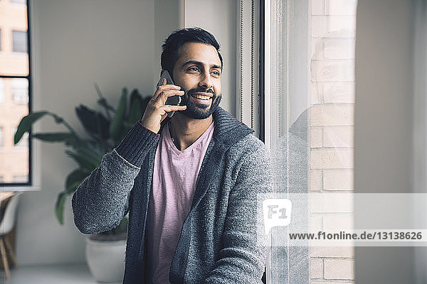 Smiling businessman talking on smart phone while sitting on window sill in office