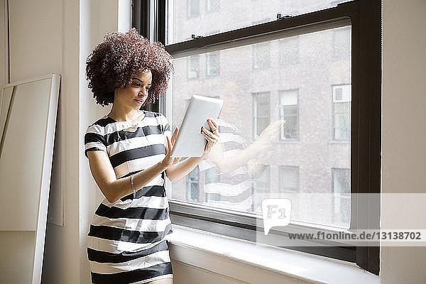 Geschäftsfrau mit Tablet-Computer am Fenster im Kreativbüro