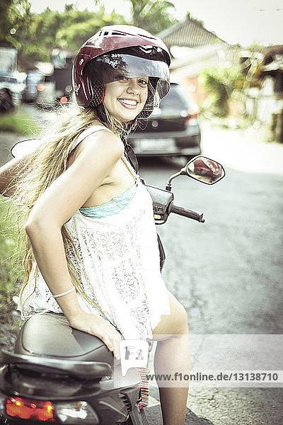 Porträt einer lächelnden Frau  die auf einem Motorroller sitzt
