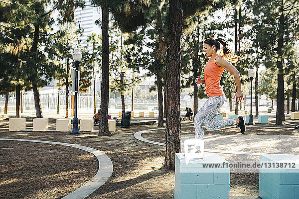 Full length side view of female athlete jumping on small columns at park