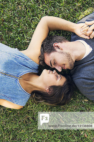 Overhead view of romantic couple lying on grass