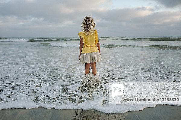 Rear view of girl standing in sea at beach