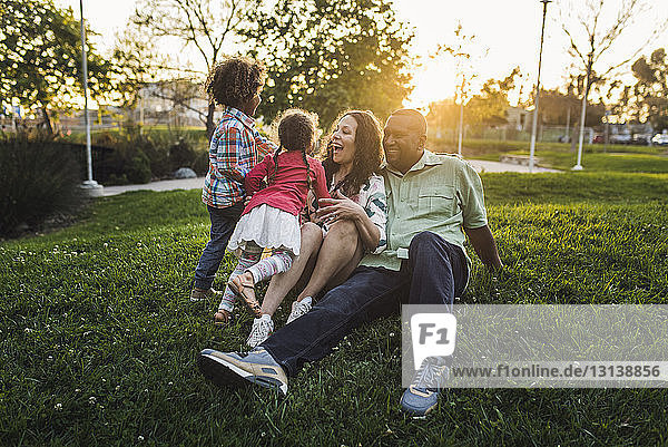 Happy family playing on grassy field at park during sunset