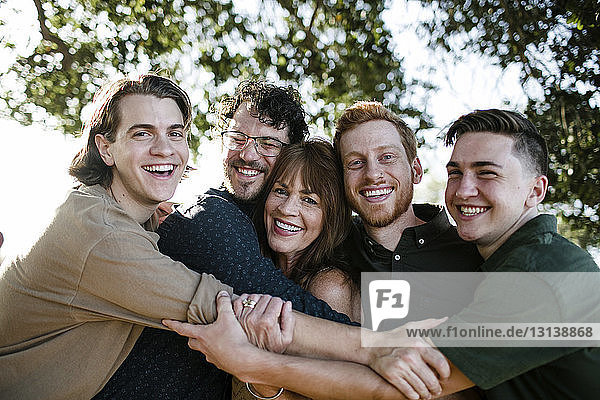 Portrait of happy sons embracing mother while standing at park