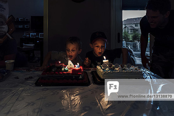 Boys with birthday cake on bed at home