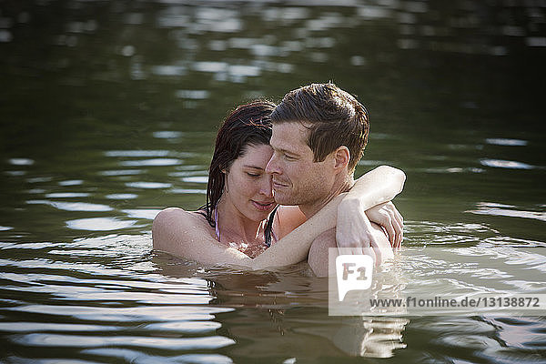 Couple embracing while standing in lake