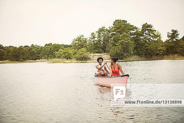 Glückliche Freunde rudern Boot auf dem See gegen den Himmel