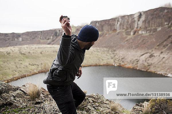 Side view of hiker throwing stone in lake while standing on cliff