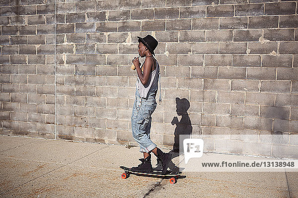Side view of woman drinking smoothie while standing on skateboard