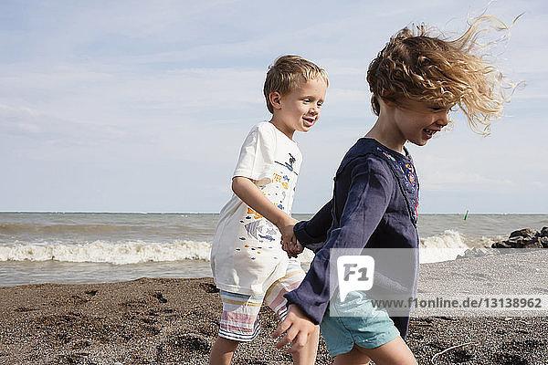 Glückliche Geschwister halten sich an sonnigen Tagen beim Spaziergang am Strand gegen den Himmel an den Händen