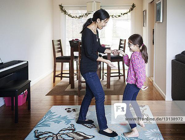 Seitenansicht einer glücklichen Mutter und Tochter  die zu Hause tanzen