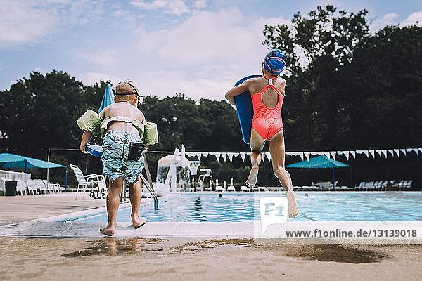 Rückansicht der Geschwister  die in den Swimmingpool springen