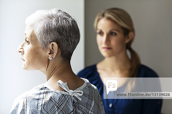 Thoughtful mother and daughter standing in hospital