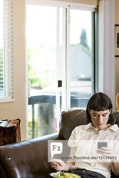 Frau telefoniert  während sie zu Hause Salat isst
