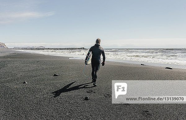 Rear view of man with surfboard walking at Black beach against sky during sunny day
