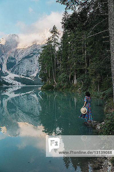 Young woman with hat standing by lake against mountains