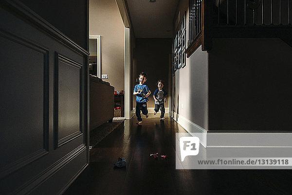 Siblings running in hallway at home